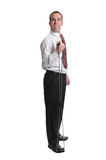 Resistance Band Exercise. Full body view of a man wearing a tie, using a resistance band, isolated against a white background Stock Photography