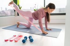 Free Resistance Band Fitness At Home Asian Woman Doing Leg Workout Donkey Kick Floor Exercises With Strap Elastic. Glute Royalty Free Stock Photography - 176611737
