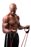 Resistance Band Training. Ripped body builder working out his biceps using a resistance band Stock Photography