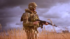 Resistand calm caucasian soldier in camoufrlage is stadning in wheat field and holding autumatic gun authentically. Isolated on dark blue sky background stock video footage