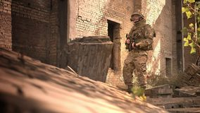 Resistant caucasian military man in camouflage standing chill near abandoned brick building, holding automatic gun and. Looking straight, fixedly stock video