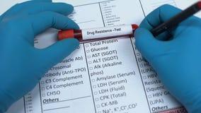 Resistencia a los medicamentos, doctor que comprueba nombre en el espacio en blanco del laboratorio, mostrando la muestra de sang almacen de metraje de vídeo