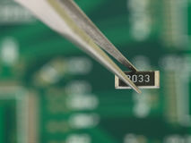 Resistor in tweezers. On green PCB background Stock Images
