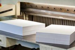 Resmas de páginas de papel cortadas em uma máquina do cortador Fotos de Stock