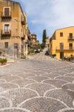 Resninggatastenläggning med motiv i staden av Castel di Tusa arkivfoto