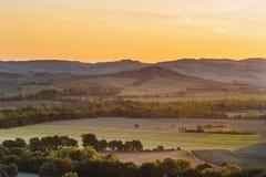 Resningsolen över de Tuscan fälten Royaltyfria Foton