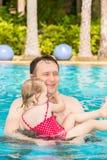 教他的小孩女儿的活跃父亲游泳在热带reso的水池 库存图片