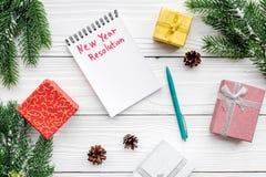 Resolución del Año Nuevo Cuaderno entre las cajas de regalo y rama spruce en la opinión superior del fondo de madera blanco Imagen de archivo