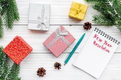 Resolución del Año Nuevo Cuaderno entre las cajas de regalo y rama spruce en la opinión superior del fondo de madera blanco Fotos de archivo libres de regalías