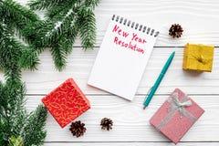 Resolución del Año Nuevo Cuaderno entre las cajas de regalo y rama spruce en la opinión superior del fondo de madera blanco Imagenes de archivo