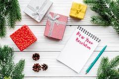 Resolución del Año Nuevo Cuaderno entre las cajas de regalo y rama spruce en la opinión superior del fondo de madera blanco Fotografía de archivo libre de regalías