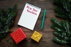 Resolución del Año Nuevo Cuaderno entre las cajas de regalo y rama spruce en la opinión superior del fondo de madera oscuro Foto de archivo libre de regalías