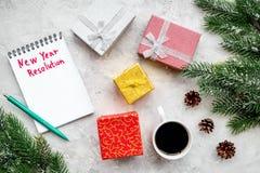 Resolución del Año Nuevo Cuaderno entre las cajas de regalo y rama spruce en la opinión superior del fondo de piedra gris Imágenes de archivo libres de regalías