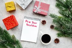 Resolución del Año Nuevo Cuaderno entre las cajas de regalo y rama spruce en la opinión superior del fondo de piedra gris Foto de archivo