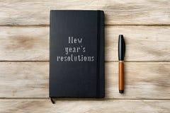 Resoluciones de los Años Nuevos del texto en un cuaderno Foto de archivo libre de regalías