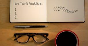 Resoluciones del Año Nuevo en libro con las gafas, la taza de café y la pluma en la tabla Fotografía de archivo libre de regalías