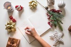 Resoluciones del Año Nuevo escritas con una mano en el cuaderno con deco de los Años Nuevos Fotografía de archivo