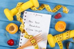 Resoluciones del Año Nuevo escritas en cuaderno en tablero azul Foto de archivo libre de regalías