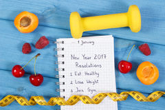 Resoluciones del Año Nuevo escritas en cuaderno en tablero azul Imagen de archivo libre de regalías
