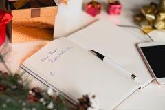 Resoluciones del Año Nuevo escritas en el cuaderno con las decoraciones de los Años Nuevos Foto de archivo