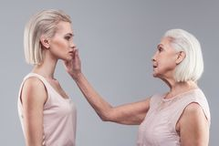 Pleasant short-haired old woman gently touching cheek of her daughter. Resolute gesture. Pleasant short-haired old women gently touching cheek of her daughter royalty free stock photos