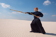 Resolute man with a training sword is practicing martial arts Royalty Free Stock Image