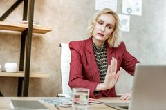 Resolute serious short-haired woman showing stopping gesture to laptop camera. Woman being unhappy. Resolute serious short-haired woman showing stopping gesture stock photo