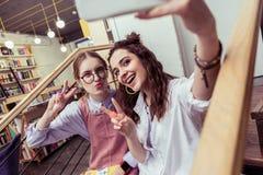 Resolute vrolijke meisjes die onnatuurlijk op gezamenlijke foto zijn royalty-vrije stock afbeelding