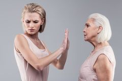 Unpleasant young lady with bob haircut stopping speech of her mother. Resolutely raising hand. Unpleasant young lady with bob haircut stopping speech of her royalty free stock image