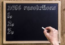 2016 resolutions. New chalkboard with 3D outlined text - on wood - with hand Royalty Free Stock Images