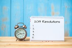 2019 Resolutions text on notebook and retro alarm clock on table and copy space. Goals, Mission and New Start Concept stock image
