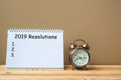 2019 Resolutions text on notebook and retro alarm clock on table and copy space. Goals, Mission and New Start. Concept stock photos