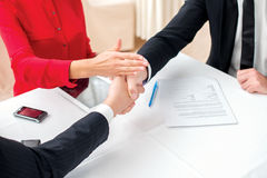 Resolve the dispute. Three successful and confident businesspeop. Le shake hands. Businesspeople in formal dress sitting in an office at a desk close-up view of Royalty Free Stock Images