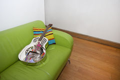 Resonator Guitar on a Green Sofa Stock Images