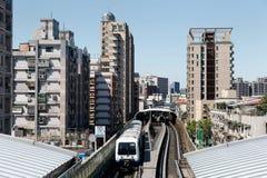 Resor för ett tunnelbanadrev på högstämda stänger mellan kontorstorn och bostads- kvarter som ankommer på en station av det Taipe Royaltyfria Foton
