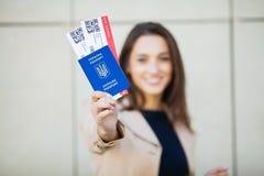 Resor Flygbiljett för kvinnainnehav två i utlandpass nära flygplats royaltyfria bilder