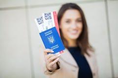 Resor Flygbiljett för kvinnainnehav två i utlandpass nära flygplats royaltyfri foto