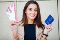 Resor Flygbiljett för kvinnainnehav två i utlandpass nära flygplats royaltyfria foton
