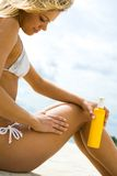At resort. Image of female with suncare lotion sitting on sandy beach Royalty Free Stock Images