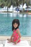 Resort. Little girl relaxes by the pool Stock Photo