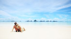 Resort. Young couple sitting on a resort's white sand and looking to a far islands on the horizon Stock Photo