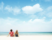 Resort. Young couple sitting on white sand by sea and looking to a blue clear sky Royalty Free Stock Photos