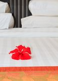Resort Bed. Clean and comfortable resort bed adorned with a red hibiscus flower royalty free stock photo
