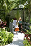Resort Bridge. Two women and a girl walking on a wooden bridge in a resort in tropical setting Stock Photography