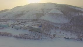Resort on frozen lake in the mountains. Aerial. Ural, Russia. Russian Ural mountains in winter. Aerial view of the lake and the endless landscapes stock video footage