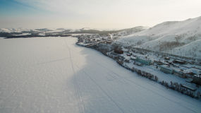 Resort on frozen lake in the mountains. Aerial. Ural, Russia Royalty Free Stock Photography