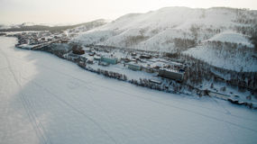 Resort on frozen lake in the mountains. Aerial. Ural, Russia Stock Photos