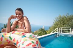 Resort Holidays And Travel, Relaxation In Luxurious House Young Happy Slender Woman Tourist With Air Donut Resting Near Swimming Royalty Free Stock Photo