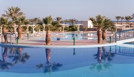 Resort hotel with a pool. Tropical resort hotel with beautiful pool in foreground Stock Image