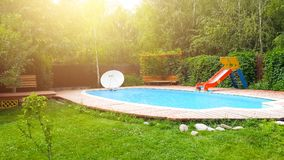 Resort house. Pool in the backyard with a slide. Holiday house with swimming pool. Resort house royalty free stock photography